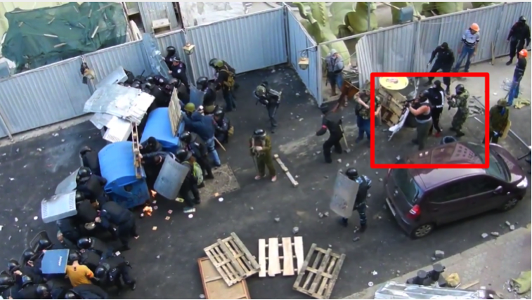 A provocateur fires an automatic rifle (screenshot from the video footage)